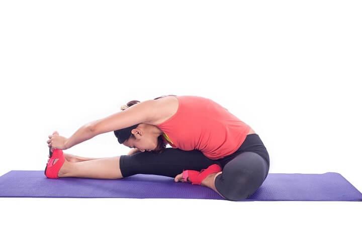Bài tập cúi người chạm đầu gối giúp co căng cơ mạng sườn, cơ tay và gập bụng