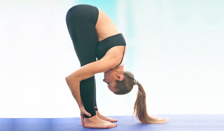 Đứng gập người là động tác Yoga giúp giảm mỡ thừa vùng trung tâm hiệu quả