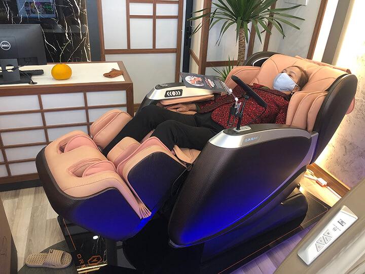 Ngồi ghế massage ngả lưng ra sau, đầu tựa thoải mái, 2 tay nẹp vào 2 bên túi khí tay, hai chân để đúng vị trí massage chân
