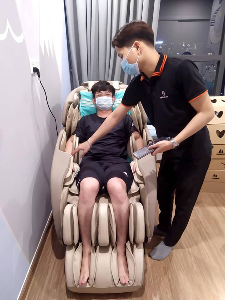 Anh Đức ngồi thử ghế massage, nghe hướng dẫn sử dụng từ nhân viên Oreni
